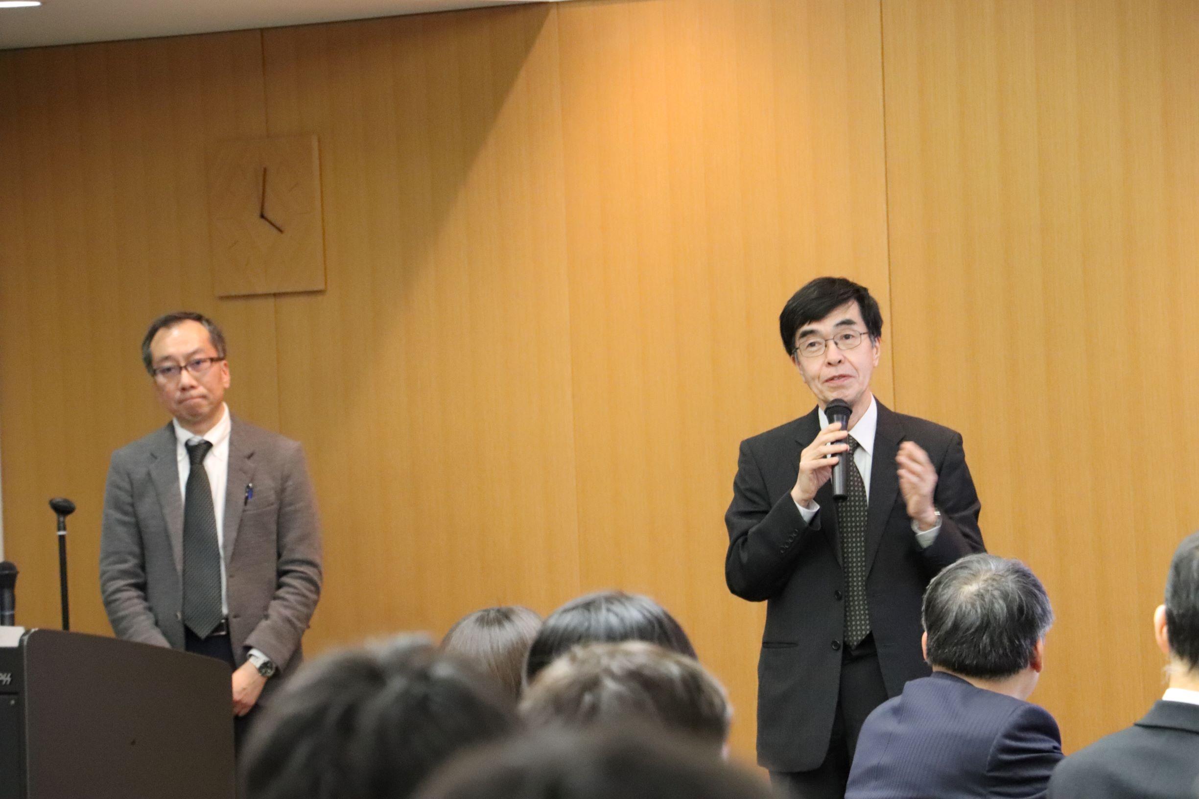 写真1 挨拶を行う小長井委員長(右)と司会の岡田幹事長(左)